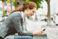 Businesswoman in a City with Mobile Phone Stock Images