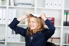 Businesswoman Clenching Teeth While Placing Documents On Head Royalty Free Stock Image