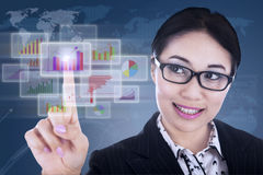 Businesswoman futuristic touchscreen. Businesswoman is clicking on futuristic touchscreen with diagrams Stock Image