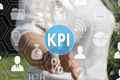 The businesswoman  clicks the button KPI, Key Performance Indica. Tor on the touch screen in the global network Royalty Free Stock Photography