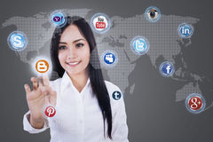 Businesswoman clicks on social network icon. Businesswoman clicks on social network on grey background Stock Images