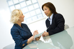 Businesswoman with client. A studio view of a businesswoman explaining a contract with a female client Stock Photos