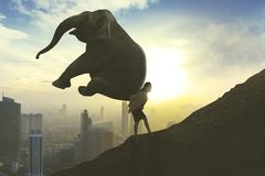 Businesswoman climb up a hill with an elephant stock photography