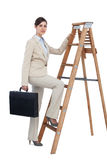 Businesswoman climbing career ladder with briefcase and looking Stock Image