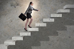 The businesswoman climbing career ladder in business concept Stock Photos