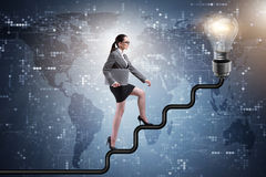 The businesswoman climbing career ladder towards light bulb Stock Image