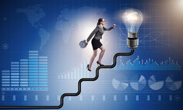 The businesswoman climbing career ladder towards light bulb Royalty Free Stock Image