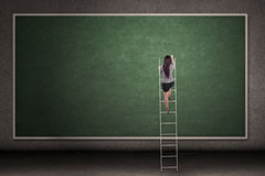 Businesswoman climbing ladder Stock Image