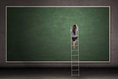 Businesswoman climbing ladder Stock Image