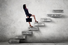 Businesswoman climbing ladder with strategy texts Royalty Free Stock Images