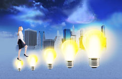 Businesswoman climbing lightbulb ladder Stock Images