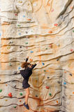 Businesswoman climbing on man-made cliff Royalty Free Stock Photography