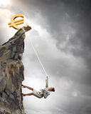 Businesswoman climbing mountain. With euro on top Royalty Free Stock Image