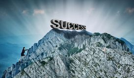 Businesswoman climbing a mountain to success stock photo
