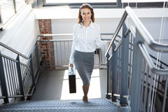 Businesswoman climbing staircase in office. Portrait of businesswoman holding a briefcase and climbing staircase in office stock image