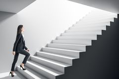 Businesswoman climbing stairs. Businesswoman climbing concrete stairs in grey interior. Success and growth concept stock image