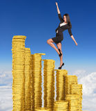 Businesswoman climbing stairs of gold coins. Sky and clouds in background Royalty Free Stock Images