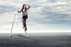 Businesswoman climbing the stairs. To the sky looking into the distance Stock Photo
