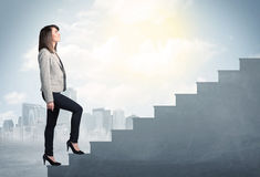 Businesswoman climbing up a concrete staircase concept Royalty Free Stock Image