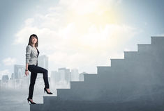 Businesswoman climbing up a concrete staircase concept Royalty Free Stock Photography