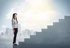 Businesswoman climbing up a concrete staircase concept Stock Photos