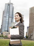 Businesswoman With Clipboard Outside Office Building Stock Image