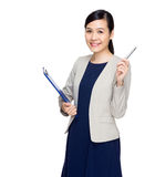 Businesswoman with clipboard and pen point up Stock Photography