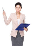Businesswoman with clipboard and pen point up Royalty Free Stock Photography
