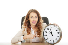 Businesswoman with clock by a desk. Shocked businesswoman with clock by a desk Stock Images