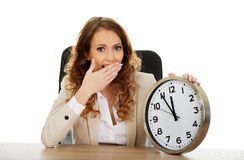 Businesswoman with clock by a desk. Royalty Free Stock Images