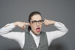 A businesswoman closes her ears and shouts stock images