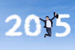 Businesswoman with cloud forming number 2015. Attractive businesswoman holding briefcase jumping on the sky and forming number 2015 with cloud Stock Photography