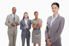 Businesswoman with co-workers applauding in the background Stock Photo