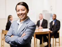 Businesswoman with co-workers in background Stock Photo