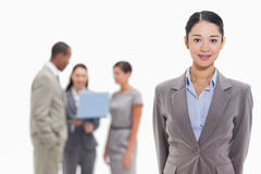 Businesswoman with co-workers watching a laptop in the backgroun Royalty Free Stock Images