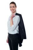 Businesswoman with coat slung over her shoulder Stock Photography