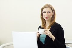 Businesswoman with coffee. A businesswoman holds a cup of coffee as she uses a laptop and smiles Stock Images