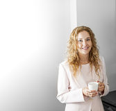 Businesswoman with coffee. Business woman in suit standing and holding coffee cup on break with copy space Royalty Free Stock Image