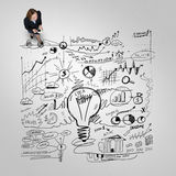Businesswoman with coffee cup. Top view of businesswoman and business strategy sketches on floor Stock Photos