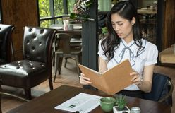 Businesswoman in a coffee shop reading a contract document Royalty Free Stock Photography