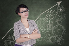 Businesswoman with cogwheel background Stock Photos