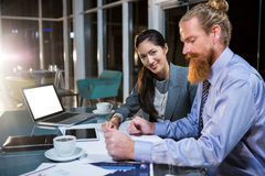 Businesswoman and colleague discussing over blueprint Royalty Free Stock Photos