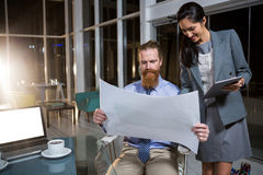 Businesswoman and colleague discussing over blueprint Stock Images