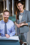 Businesswoman and colleague discussing over blueprint Stock Image