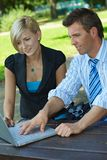 Businesswoman and colleague with laptop at park Royalty Free Stock Images
