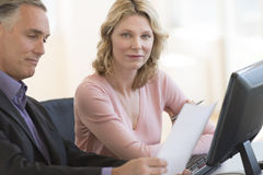 Businesswoman With Colleague Reading Document At Desk Royalty Free Stock Images