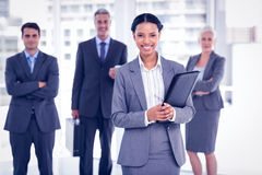 Businesswoman with colleagues behind in office Stock Photo