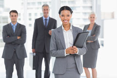 Businesswoman with colleagues behind in office Royalty Free Stock Photo