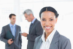 Businesswoman with colleagues behind in office Stock Images