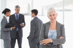 Businesswoman with colleagues behind in office Royalty Free Stock Images